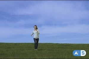Young happy woman is running and jumping by the camera blue sky and green grass on the background