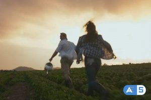 Young happy lifestyle couple running through their crop in excitement of the high amount of produce grown