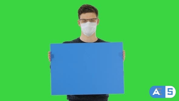 Videohive Young Man in Medical Mask Showing and Displaying Placard on a Green Screen, Chroma Key 26313180