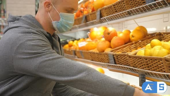 Videohive Man with Medical Face Mask Selects Lemons in Store. Guy Choose Fruits in Supermarket. Purchase Food 26163414